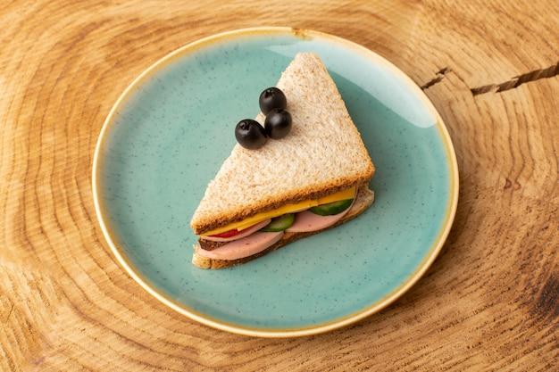 Вид сверху вкусный бутерброд с оливковой ветчиной, помидорами, овощами внутри тарелки на деревянном фоне, сэндвич, еда, закуска, завтрак