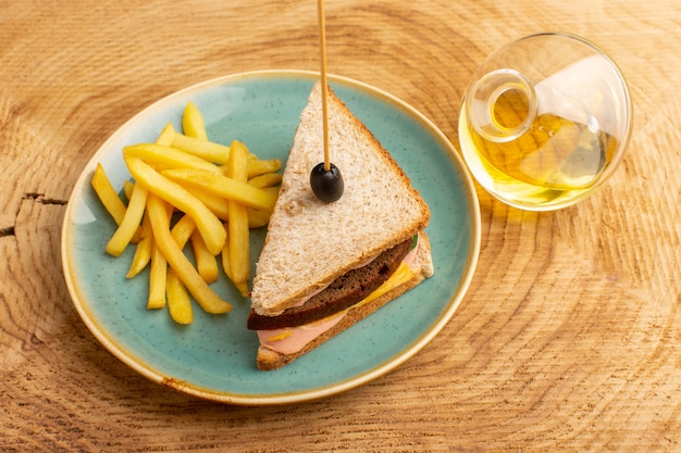 Top view tasty sandwich with olive ham tomatoes vegetables inside plate with french fries and oil on the wooden background sandwich food snack breakfast photo