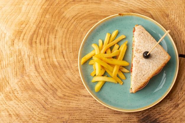 Вид сверху вкусный бутерброд с оливковой ветчиной, помидорами, овощами внутри тарелки с картофелем фри на деревянном фоне, сэндвич, еда, закуска, завтрак