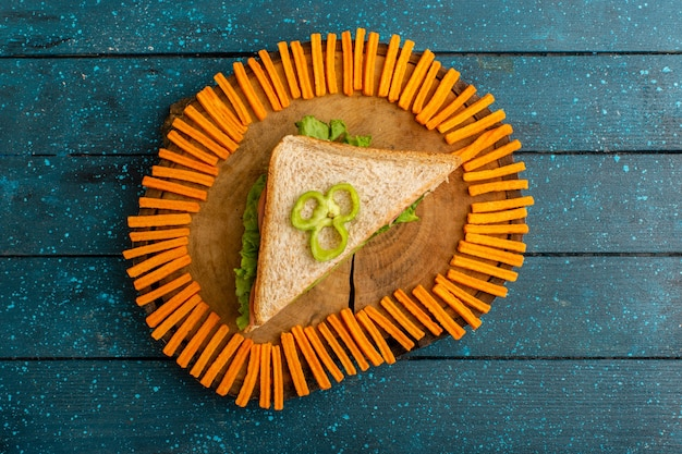 Top view of tasty sandwich with orange rusks on the blue desk
