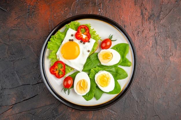 暗いテーブルのプレートの内側にスクランブルエッグとゆで卵とサラダを添えたトップビューのおいしいサンドイッチ