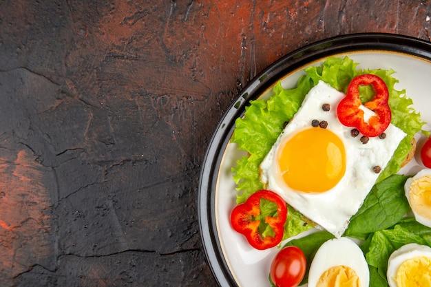 Panino gustoso vista dall'alto con uova strapazzate e sode e insalata all'interno del piatto sul tavolo scuro