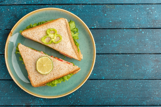 Top view of tasty sandwiches with green salad and ham inside plate