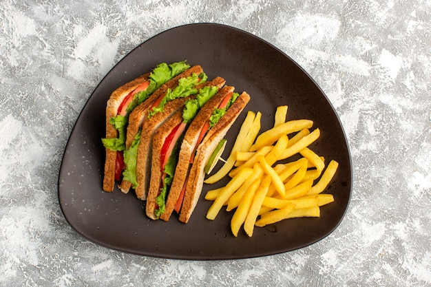 Top view of tasty sandwiches with green salad tomatoes along with french fries inside dark plate