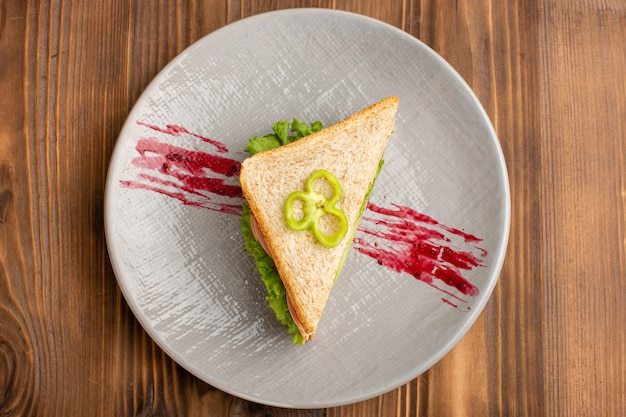 Top view of tasty sandwiches with green salad tomatoes on the brown surface