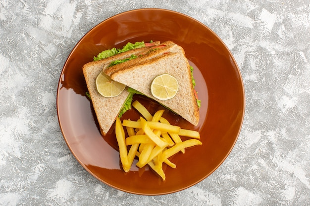 Top view of tasty sandwiches with green salad tomatoes inside brown plate