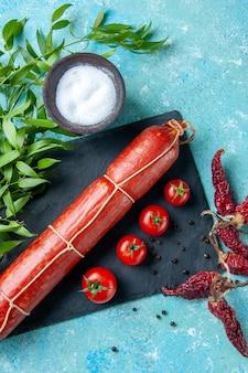 Salsiccia gustosa vista dall'alto con pomodori rossi su sfondo azzurro colore cibo hamburger farina pane a base di carne