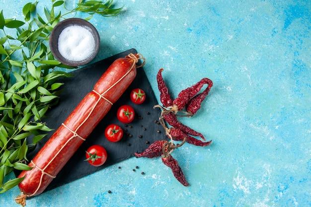 Vista dall'alto gustosa salsiccia con pomodori rossi su sfondo azzurro colore cibo hamburger panino pane