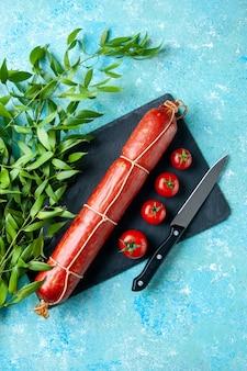 上面図水色の背景色の赤いトマトとおいしいソーセージ食品ハンバーガーミールサンドイッチ肉パン