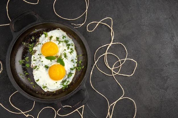 Вид сверху вкусная яичница с зеленью внутри сковороды на темном фоне завтрак хлеб еда еда обед утро омлет чай свободное пространство