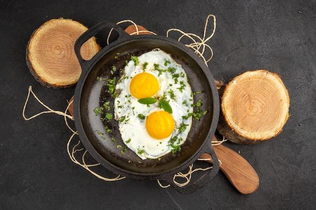 Вид сверху вкусная яичница с зеленью внутри сковороды на темном фоне завтрак хлеб еда утренний омлет чай обед