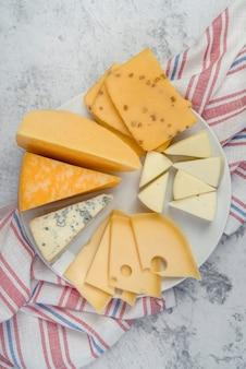 Вид сверху вкусного выбора сыра на тарелке