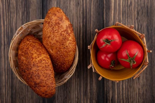 Vista dall'alto di gustosi tortini di sesamo su un secchio con pomodori rossi freschi su un secchio su uno sfondo di legno