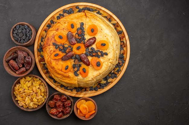 Top view of tasty shakh plov cooked rice inside round dough with raisins on dark-grey surface