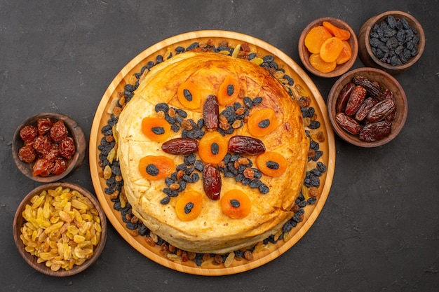 Top view of tasty shakh plov cooked rice inside round dough with raisins on grey surface
