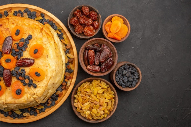 Vista dall'alto del gustoso shakh plov riso cotto all'interno dell'impasto rotondo con uvetta sulla superficie grigia