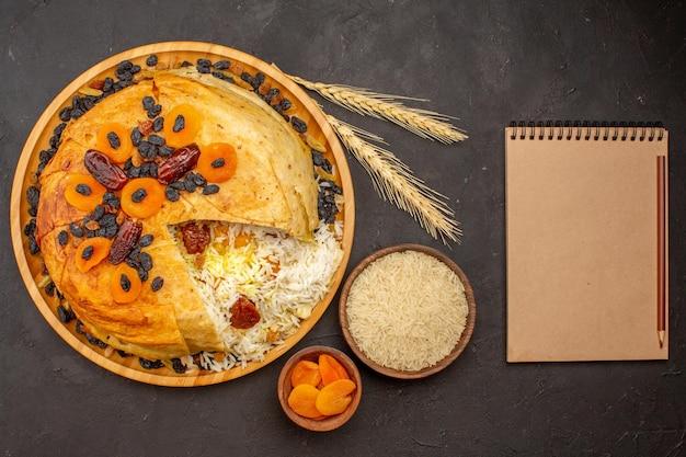 鲜美shakh plov顶视图用葡萄干和在黑暗的表面上的杏干