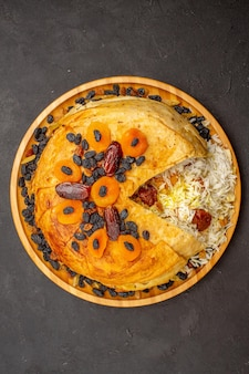 Top view of tasty shakh plov with raisins and dried apricots on dark surface