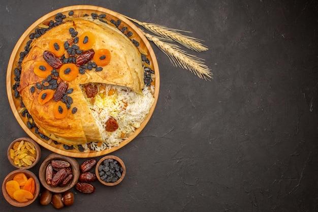Vista dall'alto del gustoso shakh plov con uvetta e albicocche secche sulla superficie scura