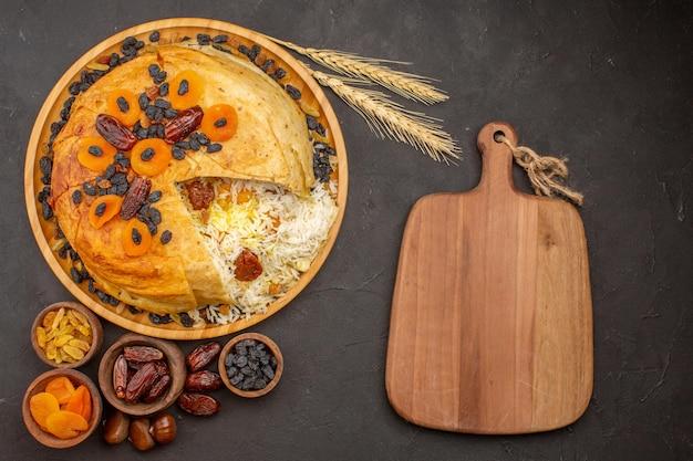 Vista dall'alto del gustoso shakh plov con uvetta e albicocche secche sulla superficie grigia