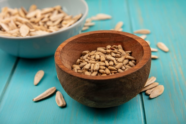 Top view of tasty shelled sunflower seeds on a wooden bowl