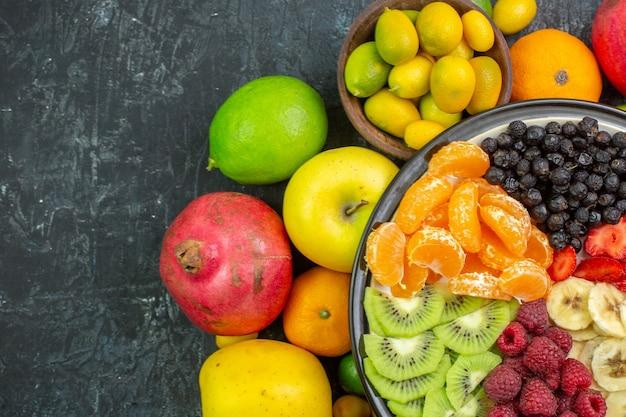 灰色の背景に新鮮な野菜とおいしいスライスフルーツの上面図