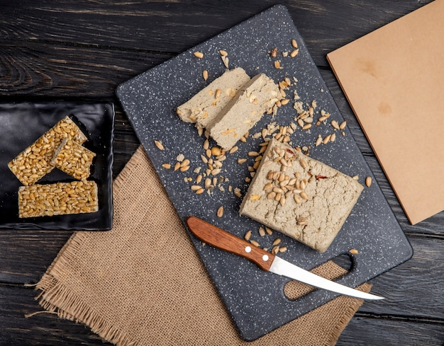 Top view of tasty slices of halva with sunflower seeds on a black cutting board