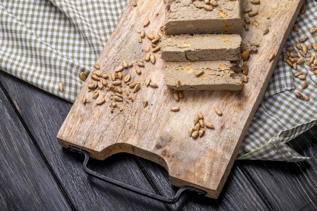 Top view of tasty slices of halva with sunflower seeds on a wooden board