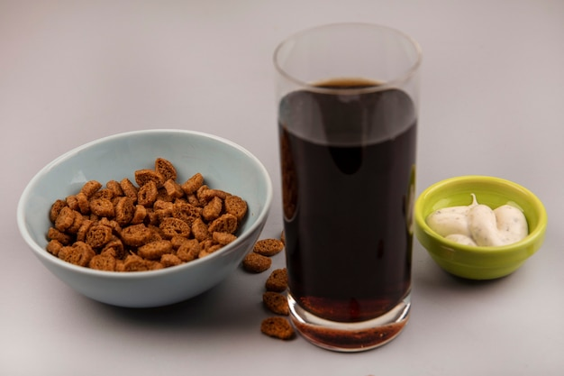 Top view of tasty small rye rusks on a bowl with a glass of cola with sauce