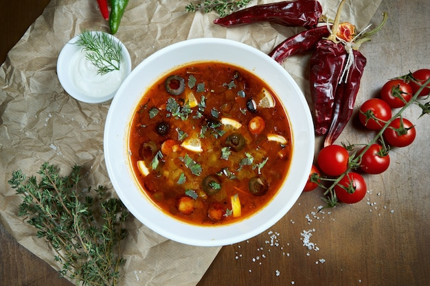 Top view on tasty solyanka thick, spicy and sour russian soup with olives, lemon and sausages in white bowl on wooden table.