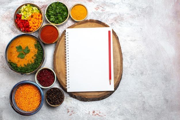 Vista dall'alto gustosa zuppa di fagioli cotti zuppa di fagioli con diversi condimenti sulla superficie bianca leggera farina di verdure pasto zuppa di fagioli di cibo