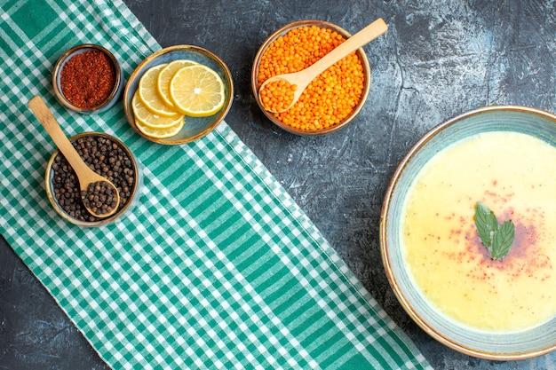 Vista dall'alto di una gustosa zuppa servita con menta e pepe, limone tritato e pisello giallo su sfondo blu