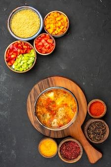 トップビューグレーの背景にさまざまな調味料とスライスしたコショウを使ったおいしいスープスープ食事食品肉調味料スパイシー