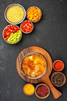 Top view tasty soup with different seasonings and sliced pepper on a grey background soup meal food meat seasoning spicy