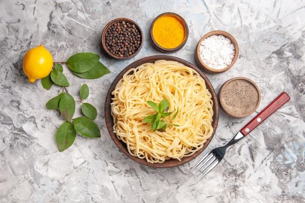 흰색 반죽 식사 파스타 접시에 조미료와 함께 상위 뷰 맛있는 스파게티