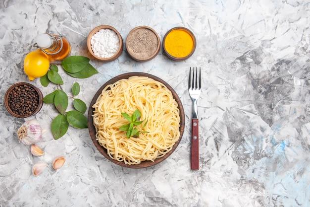 Vista dall'alto gustosi spaghetti con condimenti su pasta bianca piatto di pasta