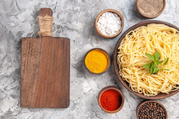 Top view tasty spaghetti with seasonings on a white dough dish pasta