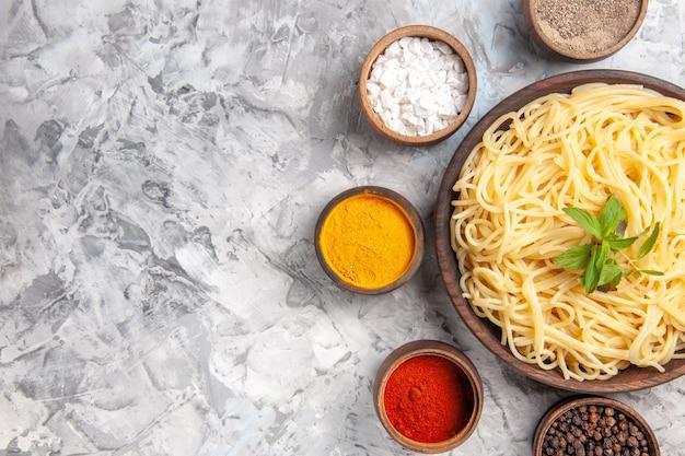 Vista dall'alto gustosi spaghetti con condimenti su un pasto di pasta bianca