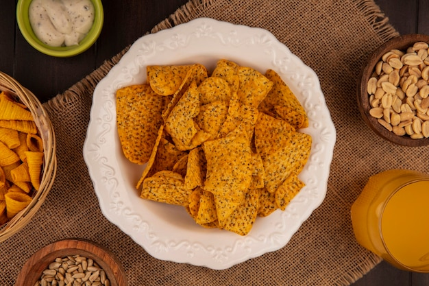 Top view of tasty spicy chips on a white bowl on a sack cloth with pine nuts on a wooden bowl with shelled sunflower seeds with a glass of orange juice on a wooden table