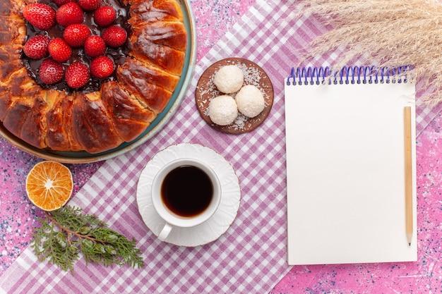 Вид сверху вкусный клубничный пирог с чашкой чая на розовом