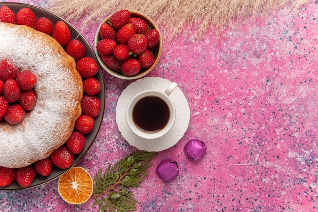 ピンクに砂糖粉を入れたトップビューのおいしいストロベリーパイ