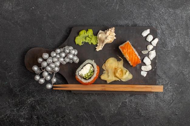 Vista dall'alto di involtini di pesce a fette di pasto gustoso sushi con wassabi e bastoncini sul muro grigio