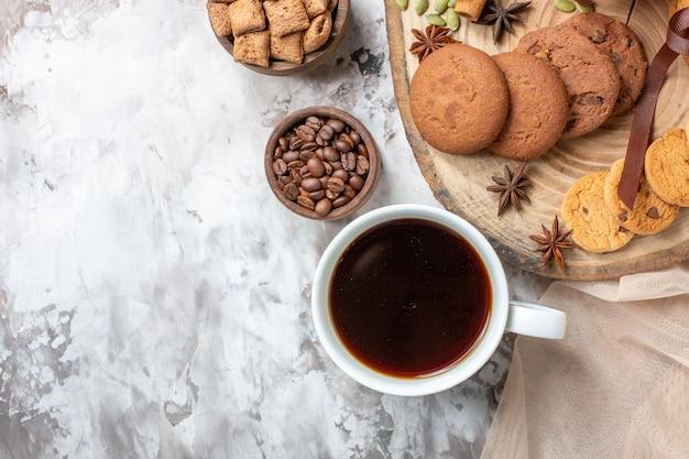 Vista dall'alto gustosi biscotti dolci con una tazza di caffè sul tavolo luminoso