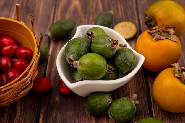 Vista dall'alto di gustosi dolci feijoas su una ciotola con ciliegie di corniola su un secchio con frutti di cachi isolato su uno sfondo di legno