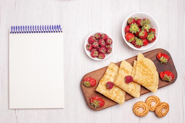 Vista dall'alto di gustosi pancake dolci con frutta su bianco