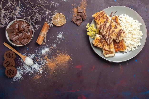 トップビューダークデスクペストリービスケットケーキシュガースウィートティーにカッテージチーズとおいしい甘いペストリー