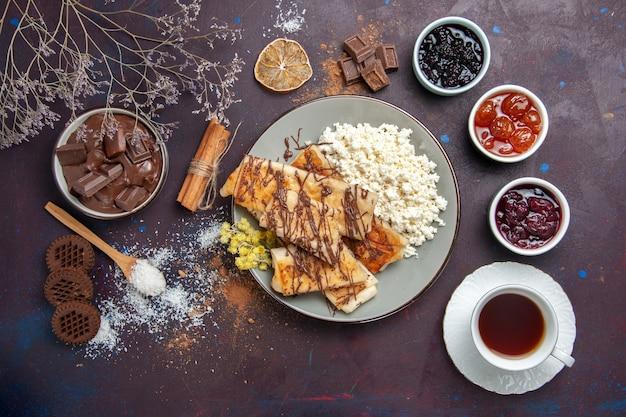 トップビュー暗い背景のペストリービスケットケーキシュガースウィートティーにお茶とカッテージチーズのカップとおいしい甘いペストリー