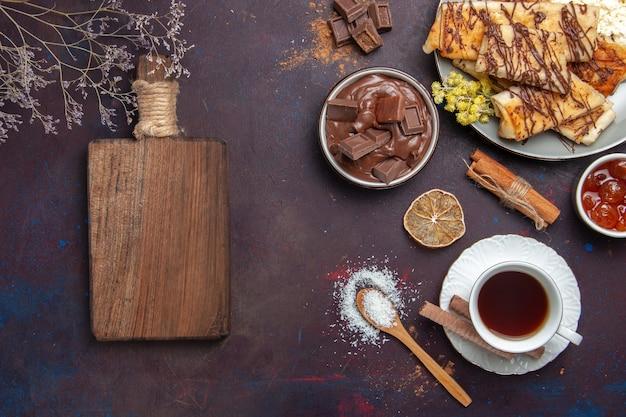 暗い背景にお茶のカップとおいしい甘いペストリーの上面図ペストリービスケットケーキ砂糖甘いお茶のデザート