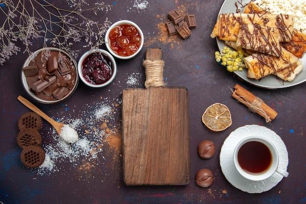 Вид сверху вкусной сладкой выпечки с чашкой чая на темном столе, печенье, бисквитный торт, сахар, сладкий чай