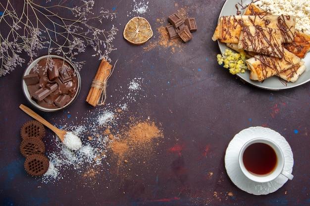 Top view tasty sweet pastries with cup of tea on dark background pastry biscuit cake sugar sweet tea